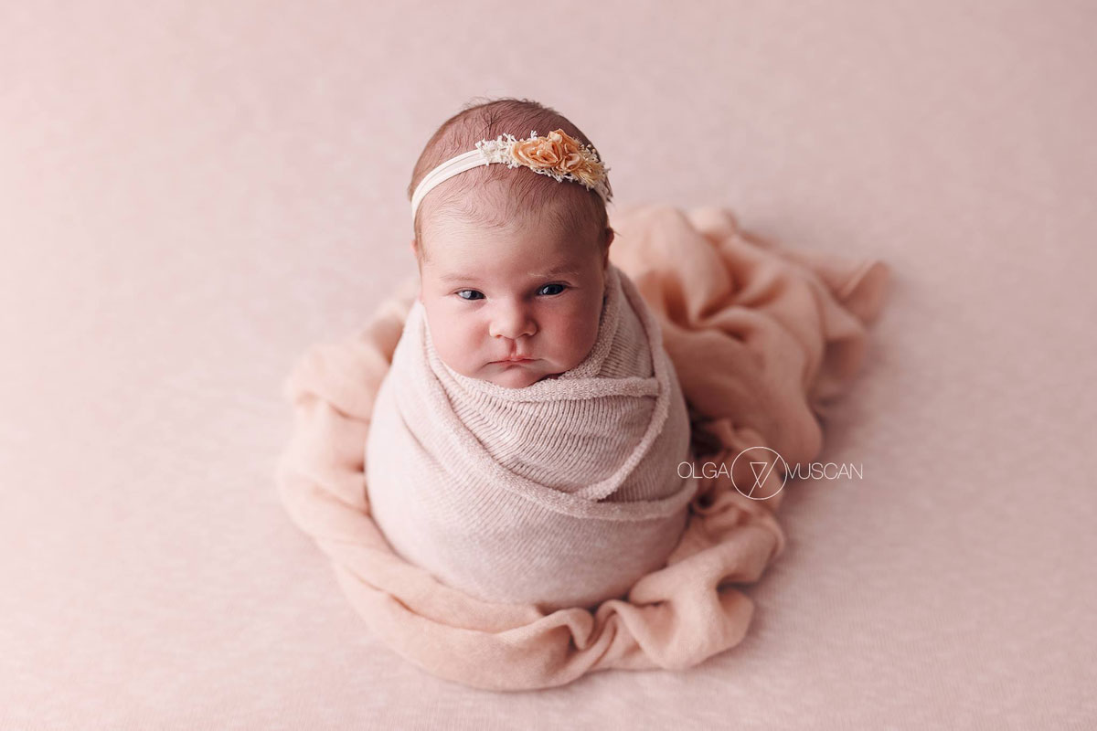 Olga Vuscan New Born Photographer for Workshops by Camen Bergmann Studio new born girl wrapped in pink looks at the camera