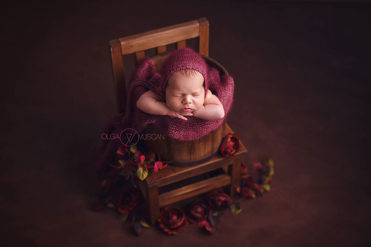 Olga Vuscan New Born Photographer for Workshops by Camen Bergmann Studio new born sleeps on a chair surounded by flowers