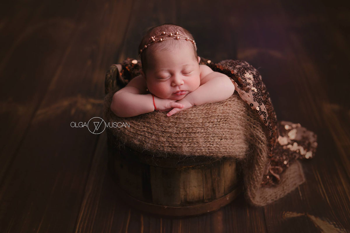 Olga Vuscan New Born Photographer for Workshops by Camen Bergmann Studio newborn gilr sleeps in a bucket on a brown floor